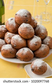 Dish with oliebollen covered with sugar, traditional Dutch pastry for New Year's Eve isolated on white background