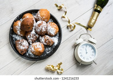dish oliebollen, oil dumpling or fritter, champagne and clock, for Dutch New Year's Eve