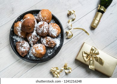 dish oliebollen, oil dumpling or fritter, champagne and gift box, for Dutch New Year's Eve