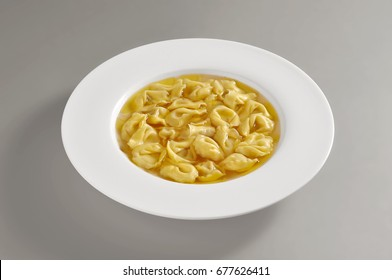 dish with portion of tortellini pasta in broth isolated on grey background