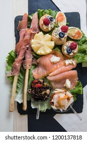 Dish prepared for an aperitif with breadsticks wrapped in slices of raw ham and canapes with cheese with raspberries and blackberries, smoked salmon and salmon with lemon Turin Italy September 2018