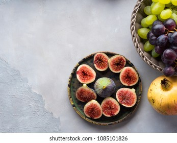 Dish of purple italian figs, basket of grapes and pomegranate on gray background. Autumn winter fruit snack still life