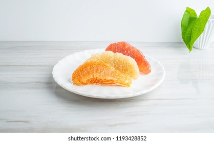 A dish of red pomelo golden pomelo and white pomelo flesh