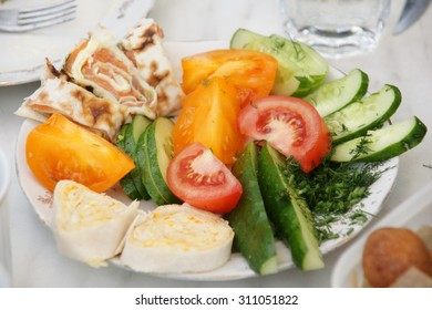 Dish with red and yellow tomatoes cucumber with dill, salad rolls on the white table in summer garden