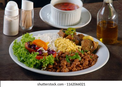 Dish with rice, beans, meat and salad
