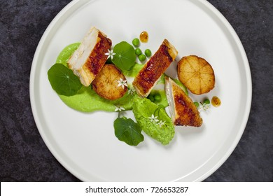 Dish of roast chicken with fondant potatoes, pea mousse, pea puree, garlic flowers and nasturtium leaves