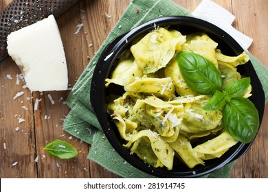 Dish of savory Italian tortelloni pasta noodles filled with ricotta and spinach and fresh basil served with pecorino and fresh salad - rucola, cherry tomatoes and mozzarella. Top view.
