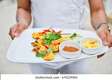 Dish of shrimp satay on hand of woman