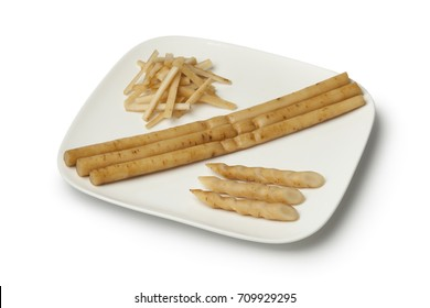 Dish with sliced Japanese pickled burdock roots called gobo on white background