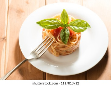 dish with spaghetti ,tomato sauce and basil on the wooden table