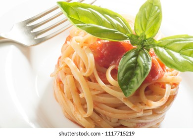 dish with spaghetti and tomato sauce on white background