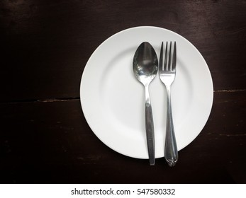 Dish and spoon on wooden background.
