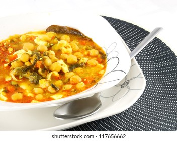 Dish of stewed chickpeas with meat, bay leaf and carrot.
