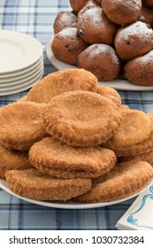 Dish with  sugared fried apple fritters or appelflappen and a dish with oliebollen on the background, traditional Dutch pastry for New Year's Eve