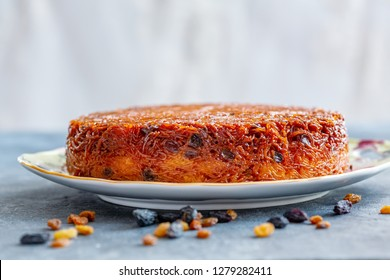 Dish with traditional Jewish dessert Kugel made of noodles, eggs, raisins and caramel on a dark gray table, selective focus.