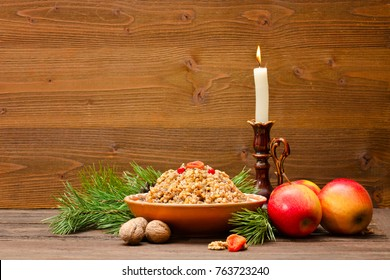Dish of traditional Slavic treat on Christmas Eve on brown wooden table. Pine branches, apples, walnuts,  candle in the candlestick. Copy space