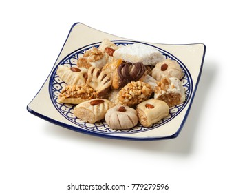 Dish with traditional variety of festive Moroccan cookies on white background
