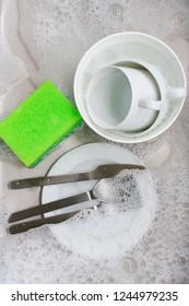 Dish washing - plate, cup, cutlery and sponge in dishwater