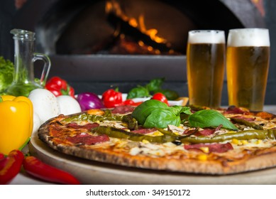 Dish which consist of delicious italian pizza made form a lot of fresh ingredients and glass of cold beer.