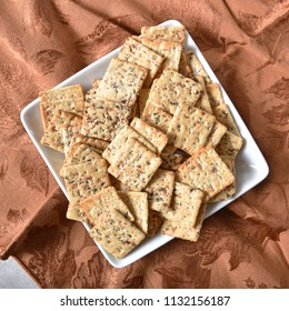 A dish of whole grain crackers loaded with garlic, onion, poppy and sesame seeds.