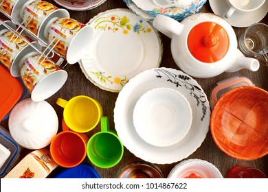 The dishes are assembled together. Dishes and tableware of different shapes and purposes. Plates, mugs, cups, a teapot are collected in a heap. Ceramic, porcelain, plastic ware. View from above.