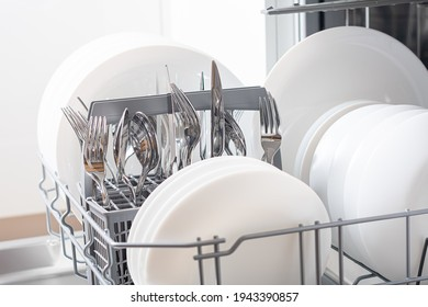 Dishes and cutlery on dishwashing machine. Clean dishes