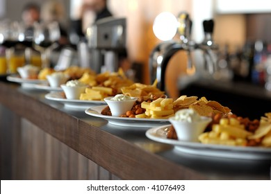 Dishes with different snacks on bar counter