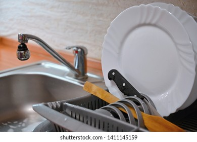 Dishes in drip tray. Clean washed dishes in the kitchen.