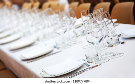 Dishes, empty glasses, white napkins, forks and knifes on white tablecloth, selective focus