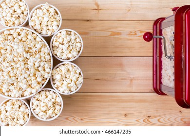 Dishes of fresh popcorn arranged in a decorative circle around a larger center bowl alongside a machine on a wooden table with copy space