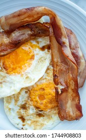 dishes of fried bacon and fried egg for breakfast