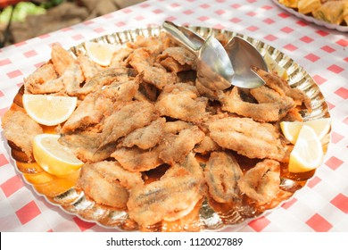 Dishes of fried and breaded food for a wedding in the countryside outdoors in the summer.