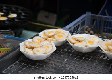 Dishes full of small fried quail eggs at asian market