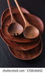 The dishes, plates and spoon made of wood on a dark stone background.  - Shutterstock ID 1728146452