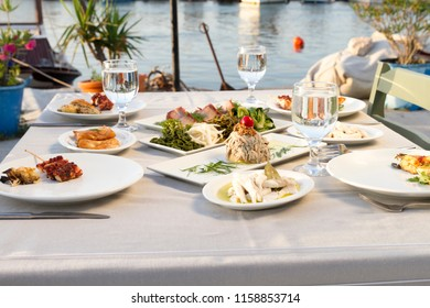 Dishes with various seafood at dinner table near the sea view. Restaurant that specializes in seafood cuisine such as fish and shellfish.