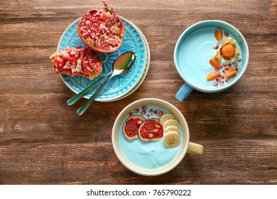 Dishes of yummy spirulina smoothie and plate with pomegranate on wooden table. Healthy vegan food concept