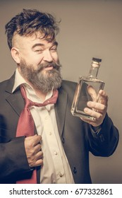 Disheveled adult bearded man in suit holding a glass bottle. Toned