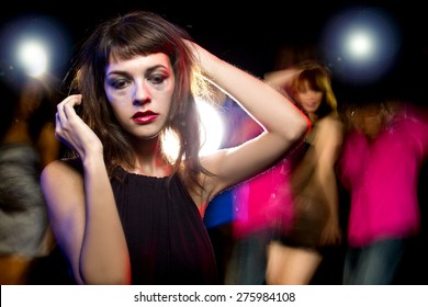 Disheveled drunk or female high on drugs at a nightclub.  Motion blurred party people in the background dancing.