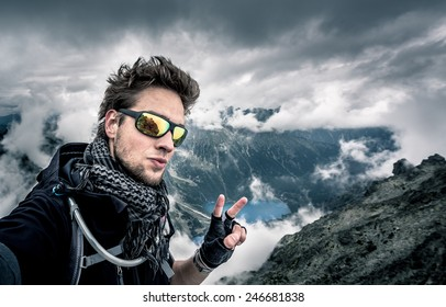 Disheveled man, with tousled hair on top of the mountain showing the peace sign, with lakes and low clouds in the background