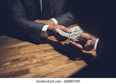 Dishonest businessman secretly giving money to his partner in the dark - bribery, scam and venality concepts