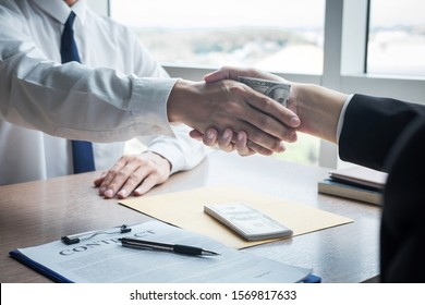 Dishonest cheating in business illegal money, Businessman handshake with money of dollar banknotes in hands from while give success the deal, Bribery and corruption concept.