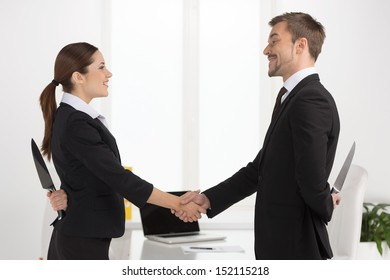 Dishonest partnership. Two young business people shaking hands and holding knifes behind their backs.
