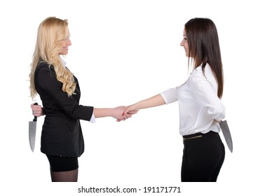 Dishonest partnership. Two young business woman shaking hands and holding knifes behind their backs.