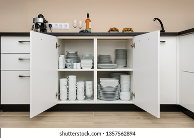 Dishware storage cabinet with open doors, white plates, bowls cups and other china crockery inside, front view