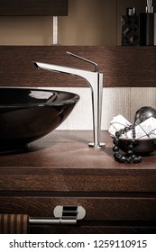 Dishwasher basin and modern aesthetic basin mixer on wooden table.