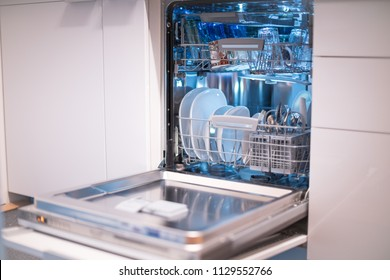 Dishwasher with dishes in kitchen furniture.