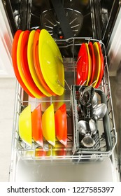 Dishwasher with fresh clean colordul flatware, selective focus, vertical shot