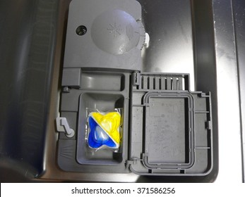 Dishwasher tablets in an open container inside the appliance