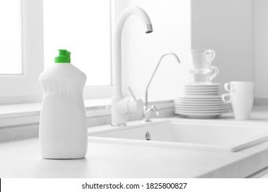 Geschirrspülflasche auf Küchenwaschbecken und sauberem Hintergrund