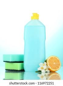 Dishwashing liquid with sponges and lemon with flowers on blue background